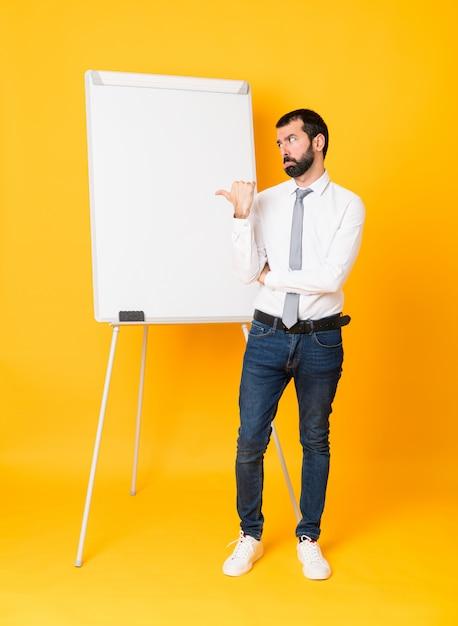 Foto de cuerpo entero del empresario dando una presentación en pizarra sobre amarillo aislado infeliz y apuntando hacia el lado Foto Premium