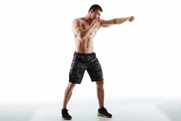Foto de cuerpo entero del hombre semidesnudo fuerte en pose de boxeo Foto gratis