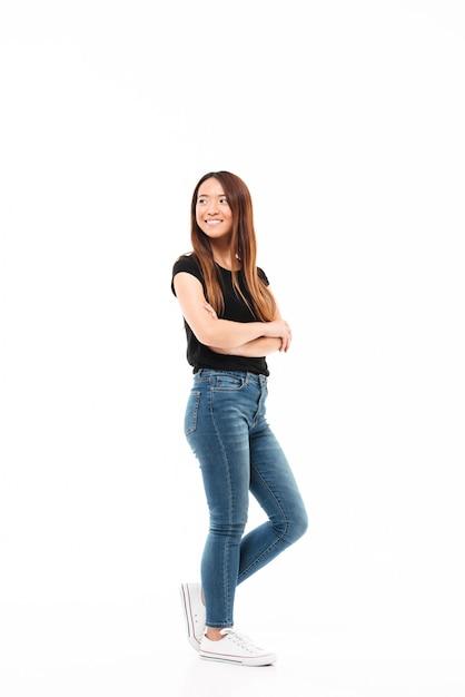 Foto de cuerpo entero de la joven y bella mujer china en camiseta negra y jeans de pie con las manos cruzadas, mirando a un lado Foto gratis