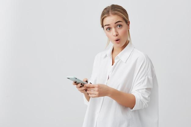 Foto de empresaria sorprendida con cabello rubio vestido con una camisa blanca sosteniendo su moderno teléfono inteligente recibiendo un mensaje sorprendido al olvidarse de una reunión importante con socios comerciales Foto gratis