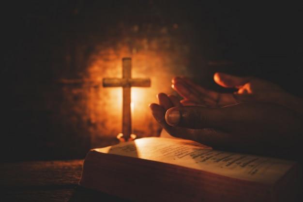 Foto de época de la mano con la biblia orando. Foto gratis
