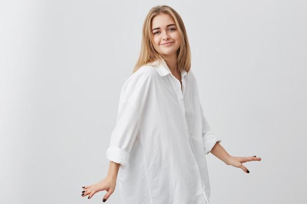 Foto de estudio de joven inconformista europeo femenino con cabello rubio vestido con camisa blanca de gran tamaño posando en el interior en la pared en blanco. chica guapa con expresión complacida de cara sonriendo y posando en la cámara. Foto gratis