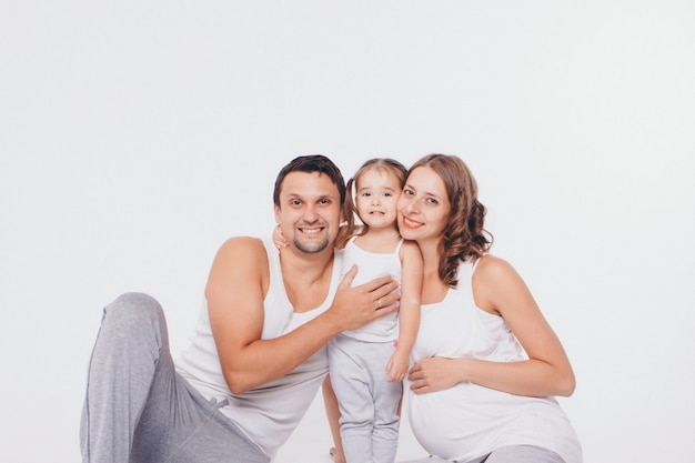 Foto de familia sobre un fondo blanco, los padres pasan tiempo con sus hijos. mamá y papá abrazan al bebé. Foto Premium