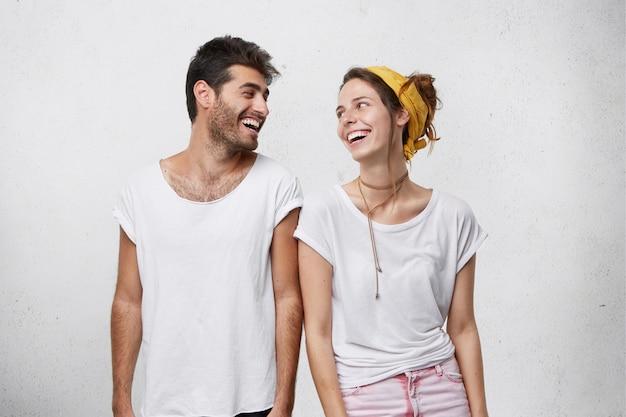 Foto de hombre guapo con cabello oscuro y linda mujer mirando el uno al otro con amplias sonrisas que son alegres de encontrarse. Foto gratis