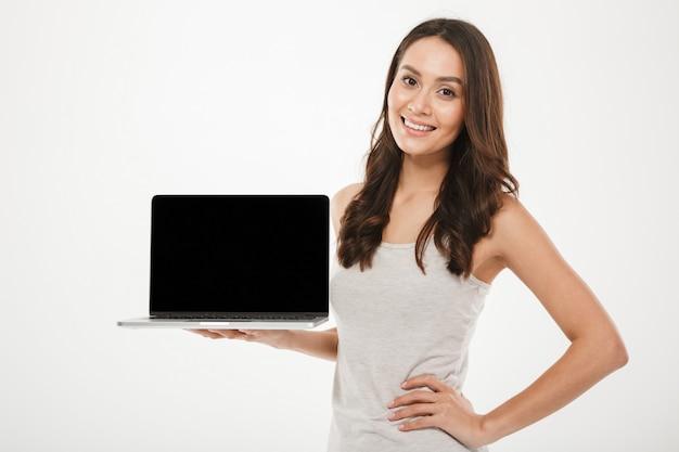 Foto horizontal de mujer educada complacida sonriendo y demostrando una pantalla vacía negra de plata portátil sosteniendo en la mano, sobre pared blanca Foto gratis
