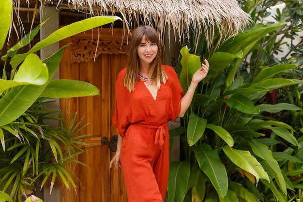 Foto de moda de verano al aire libre de mujer hermosa en traje boho posando en resort de lujo tropical. Foto gratis