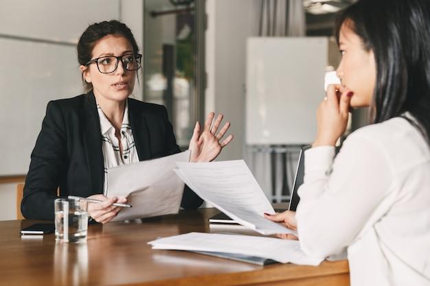 Foto de mujer caucásica estricta con currículum vitae y negociar con la candidata durante una reunión corporativa o una entrevista de trabajo: concepto de negocio, carrera y colocación Foto Premium
