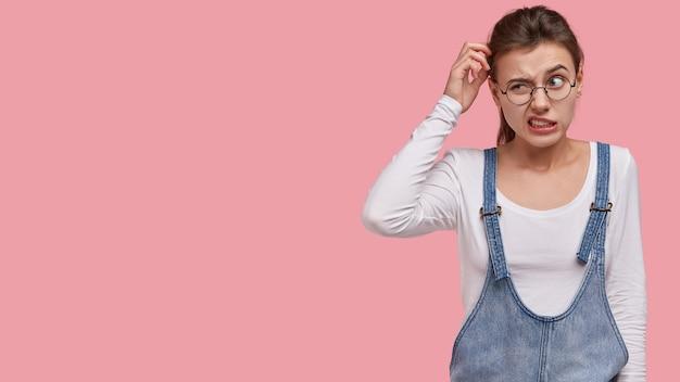 Foto de mujer desconcertada se rasca la cabeza con desconcierto, piensa en encontrar la solución adecuada, viste sarafan de moda Foto gratis