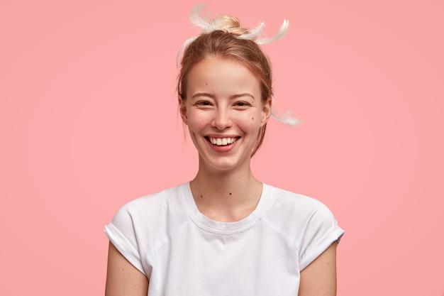 Foto de mujer feliz se despierta temprano en la mañana de buen humor, tiene un aspecto atractivo, viste una camiseta informal, aislada sobre una pared rosa. mujer alegre se regocija el fin de semana disfruta de un sueño prolongado y sueños agradables Foto gratis