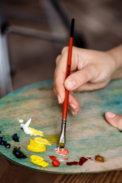 Foto de mujer mezclando pinturas al óleo sobre paleta de cerca Foto gratis