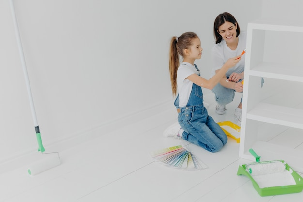 Foto de niña y su madre pintan muebles para nuevo departamento Foto Premium