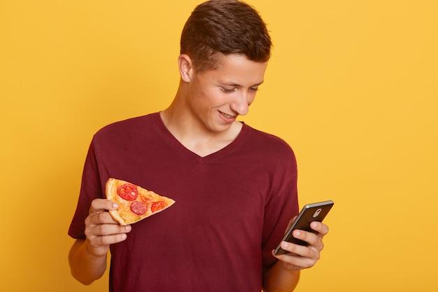 Foto de ocupado adolescente alegre curioso sosteniendo su teléfono inteligente, usando su dispositivo, revisando los sitios de redes sociales Foto gratis