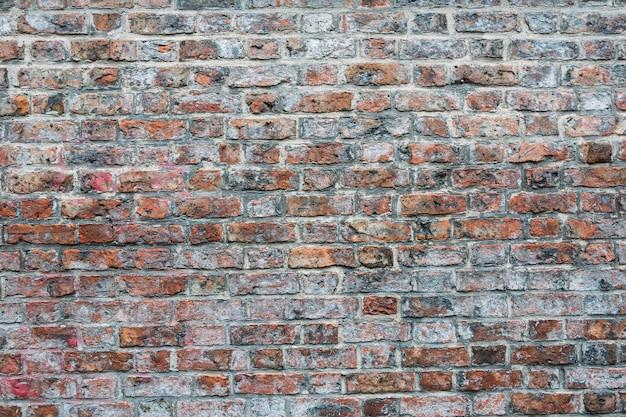 Foto de una pared de ladrillos cementados de color rojo y marrón - ideal para fondos de pantalla Foto gratis