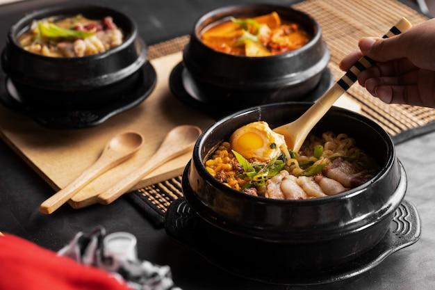 Foto de una persona comiendo comida china con una cuchara de una placa negra Foto gratis
