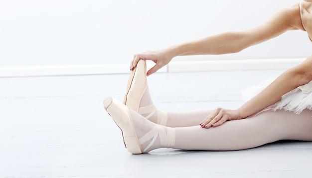 Foto de los pies de la hermosa bailarina durante el estiramiento Foto gratis