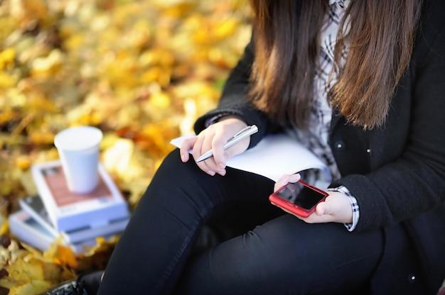 Foto del primer de la muchacha asiática del estudiante que usa su teléfono móvil durante estudiar / el trabajo Foto Premium