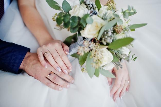Foto de primer plano de las manos del novio y la novia con anillos y bouquet. Foto Premium