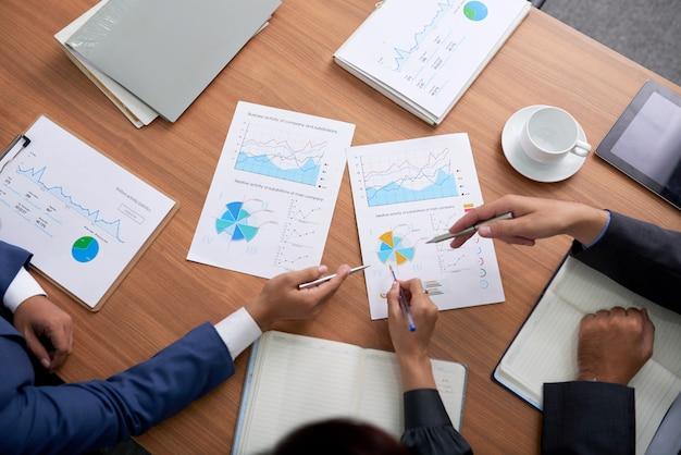 Foto principal de tres empresarios irreconocibles sentados en una reunión y mirando gráficos Foto gratis
