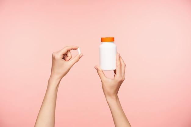 Foto recortada de las manos bien arregladas de la hembra levantada sosteniendo una pastilla blanca y un frasco con tapa naranja, tomando vitaminas mientras posa sobre un fondo rosa Foto gratis