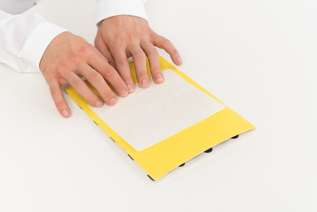 Foto recortada de manos de un hombre leyendo braille. Foto Premium