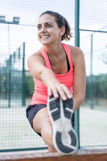Foto vertical de una mujer en ropa deportiva estirando su pierna en un tenis al aire libre Foto Premium