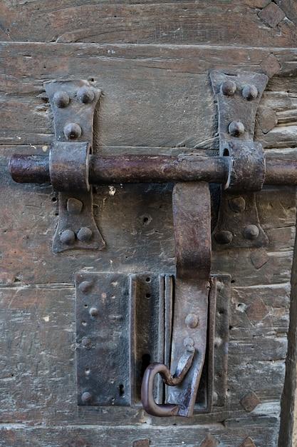 Foto vertical de una vieja cerradura de una puerta oxidada y con la madera vieja. villefranche de conflent en francia Foto Premium
