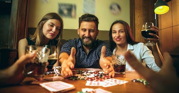 Foto de vista lateral de amigos masculinos y femeninos sentados en la mesa de madera. hombres y mujeres jugando al juego de cartas. manos con primer plano de alcohol. poker, entretenimiento nocturno y concepto de emoción. Foto gratis