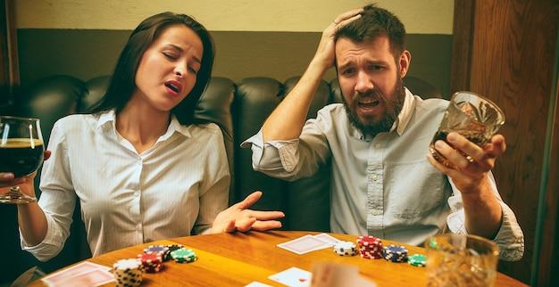 Foto de vista lateral de amigos masculinos y femeninos sentados en la mesa de madera. hombres y mujeres jugando al juego de cartas. manos con primer plano de alcohol. Foto gratis