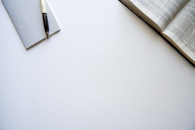 Fotografía cenital de una biblia abierta y un bloc de notas con un bolígrafo sobre una superficie blanca Foto gratis