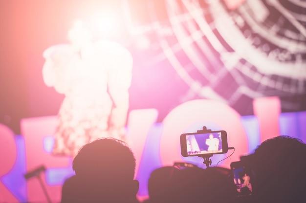 Fotografiando con smartphone en concierto. Foto Premium