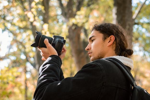 Fotógrafo aficionado de la naturaleza tomando fotos en el bosque de otoño Foto Premium