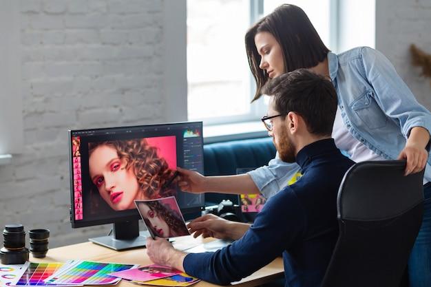 Fotógrafo y diseñador gráfico que trabaja en la oficina con computadora portátil, monitor, tableta de dibujo gráfico y paleta de colores. Foto Premium