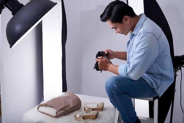 Fotógrafo masculino asiático sentado en el estudio y tomando fotos de accesorios de moda Foto gratis