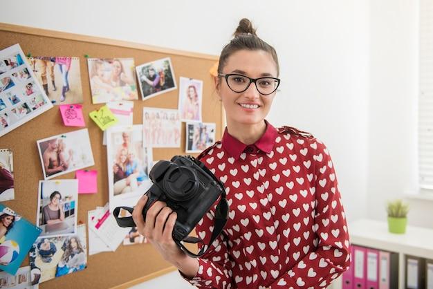 Fotógrafo profesional posando con su cámara Foto gratis
