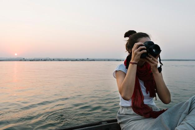 Fotógrafo de sexo femenino que se sienta en un barco en el río ganges Foto gratis