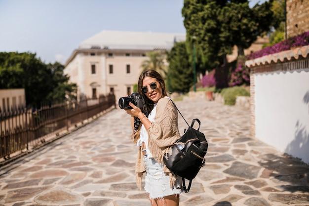 Fotógrafo de sexo femenino con su mochila de pie en la calle
