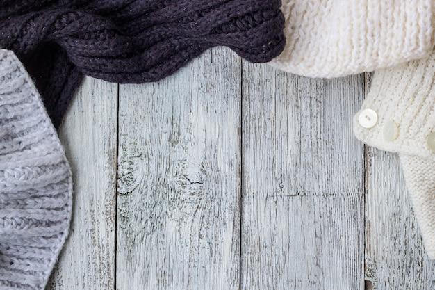 Fragmento de ropa de tejer en el fondo de madera blanco Foto Premium