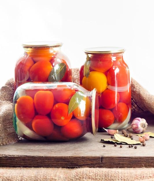 Frascos de vidrio con tomates rojos en escabeche, sellados con tapa de metal Foto Premium