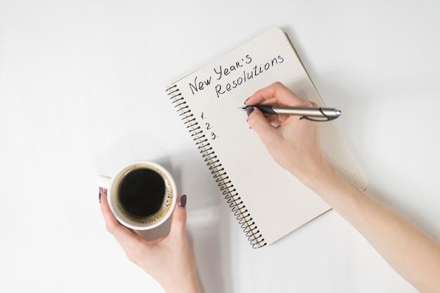 Frase de resoluciones de año nuevo en el cuaderno, mano femenina con bolígrafo y taza de café Foto Premium