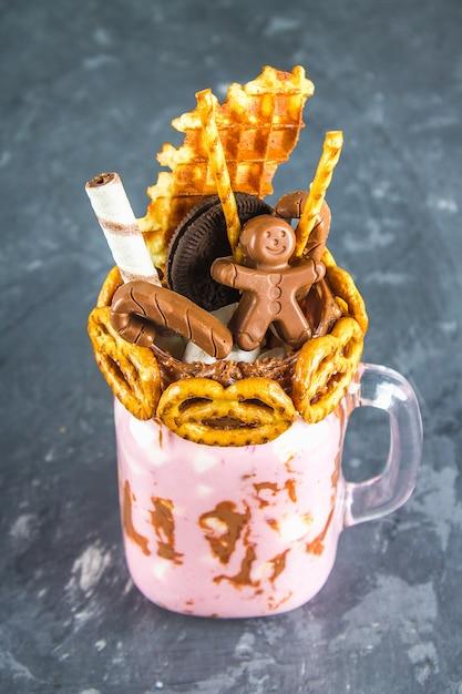 Freakshake de batido rosa, crema. monstershake con un hombre de chocolate, caña Foto Premium