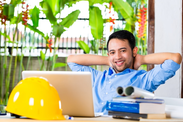 Freelance - arquitecto trabajando en casa en un diseño o borrador, en su escritorio hay libros, una computadora portátil y un casco o casco Foto Premium