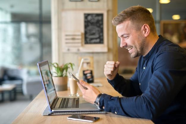 Freelancer feliz con tableta y computadora portátil en cafetería Foto gratis