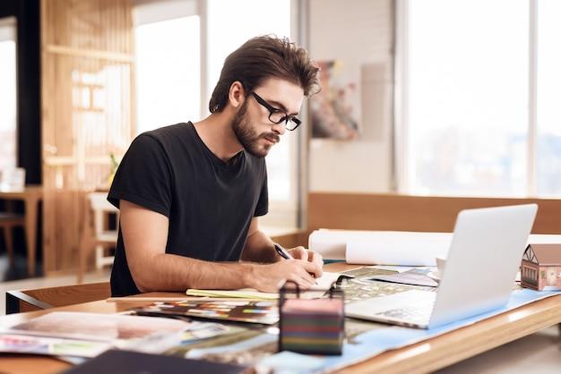 Freelancer hombre barbudo tomando notas en la computadora portátil. Foto Premium