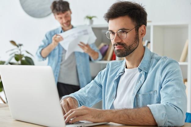 Freelancer hombre barbudo trabaja en computadora portátil, información de teclados, piensa en ganancias Foto gratis