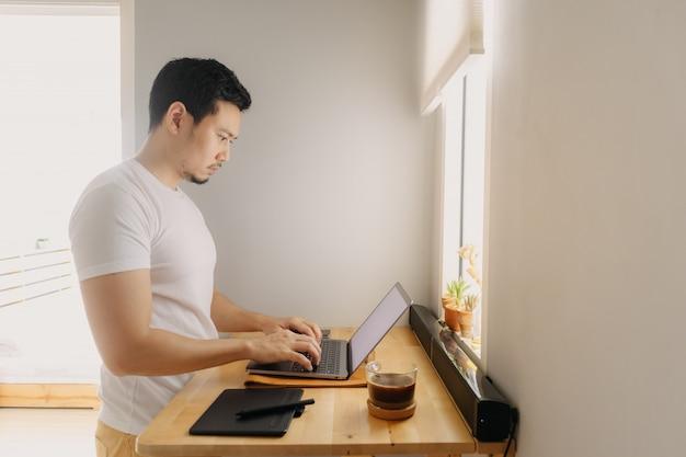Freelancer hombre está trabajando en su computadora portátil en su apartamento. concepto de trabajos creativos freelance. Foto Premium