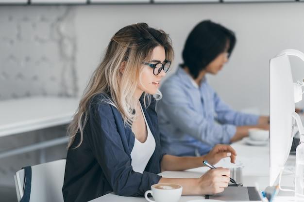 Freelancer mujer ocupada con cabello largo trabajando con tableta y tomando café. retrato de interior de estudiante japonés concentrado usando computadora en el aula. Foto gratis