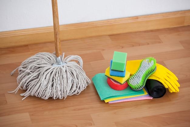 Fregona y equipo de limpieza en piso de madera Foto Premium