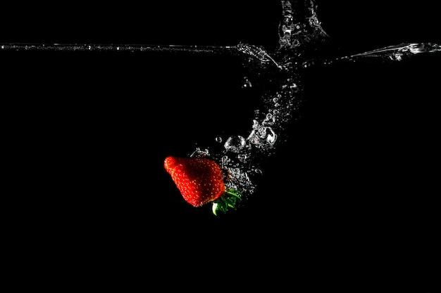 Fresa en agua con fondo negro. Foto Premium