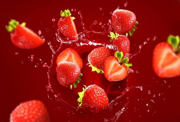 Fresa cayendo en el lote de jugo Foto gratis