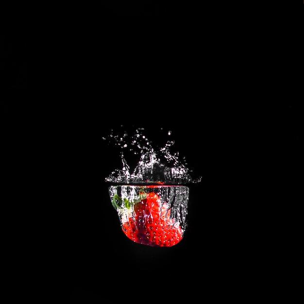 Fresa sumergiéndose en el agua Foto gratis